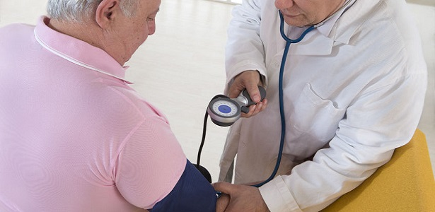 doctor checking blood pressure of his patient fat man